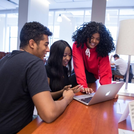 Three students looking at a laptop together